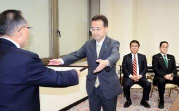 山崎正昭会長(左)から推薦証を受け取る杉本達治氏(左から2人目)=12月25日、福井市の福井県繊協ビル
