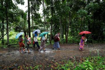 26日、インドネシアのバンテン州で、傘をさしながら避難所に向かう人々(ロイター=共同)