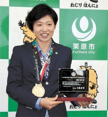 アジア大会の金メダルを首に掛け、栄誉の楯を手にする狩野選手