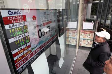 2万円を割り込んだ株価を表示するボードに見入る個人投資家=25日午後1時ごろ、仙台市青葉区の証券会社