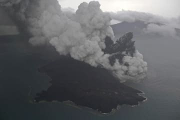 23日、インドネシアのスンダ海峡で噴煙を上げるアナック・クラカタウ山(AP=共同)