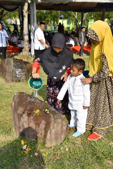2004年のスマトラ沖地震から14年を迎え、インドネシア・アチェ州の集団墓地で、花を手向ける子どもたち=26日(共同)