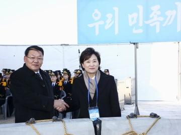 26日、北朝鮮・開城の板門駅で開かれた着工式で握手する韓国の金賢美国土交通相(右)と北朝鮮のキム・ユンヒョク鉄道次官(韓国取材団・共同)