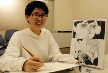 「ヘドロの子」の一場面のページを傍らに置き、新作を描く亀島さん