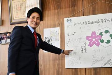 自分のサインを指さし、笑顔を見せる木浪=26日午後、青森市の青森山田高校