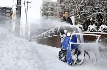 朝から冷え込んだ札幌市内で、歩道の雪かきに追われる男性=27日午前