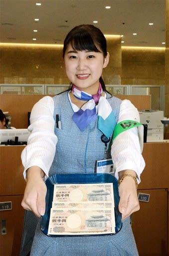 肥後銀行の窓口で2千円札を差し出す行員。手数料を払うと窓口で両替できる=熊本市中央区