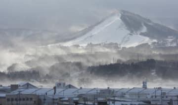 冬型の気圧配置に伴う強い西風で新雪が舞う青森市雲谷スキー場周辺=27日午前9時25分、同市第二問屋町の東奥日報社から