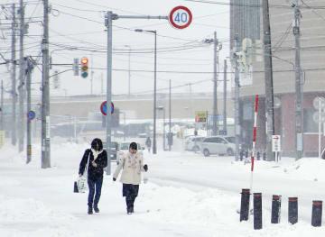 青森市内で雪が積もった道路を歩く人たち=27日午後