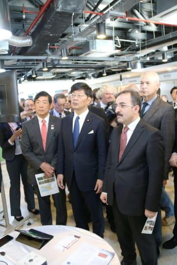 27日、アンカラで開かれた日トルコ防災セミナーの会場で、企業の展示ブースを見学するチャタクル内務副大臣(手前右)と、阿達雅志政務官(中央)ら(共同)