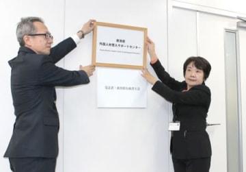 「県外国人材受入サポートセンター」が開所し、看板を掛ける県職員ら=27日、新潟市中央区