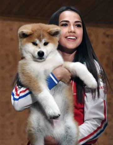 贈呈された秋田犬の子犬を抱き、笑顔のアリーナ・ザギトワ選手=5月26日、モスクワ(共同)