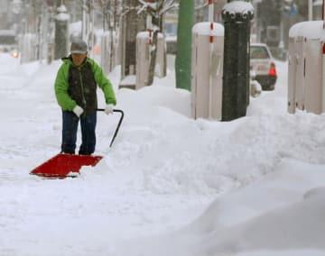 青森市内で雪かきをする男性=28日午前