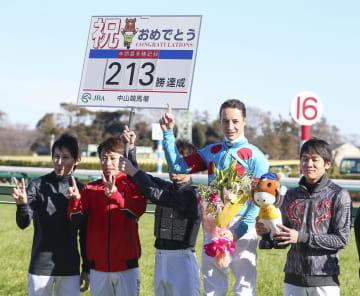 JRA年間最多勝利記録を13年ぶりに更新する213勝を挙げ、祝福されるクリストフ・ルメール騎手(右から2人目)=28日、中山競馬場