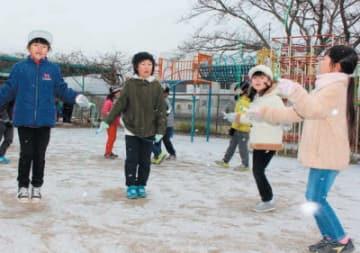 雪が舞う中、元気に遊ぶ子どもたち=28日午前9時20分、玖珠町
