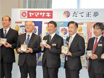 だて正夢の米粉パンをPRする村井知事(中央)と酒井工場長(左から2人目)