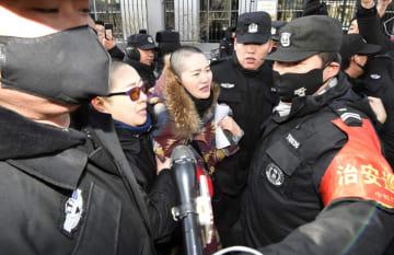 中国の人権派弁護士、王全璋氏の公判手続きの違法性を訴え北京市の最高裁を訪れ、公安当局の関係者らに取り囲まれる妻、李文足さん(中央)=28日(共同)