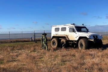ウクライナ本土とロシアが実効支配するクリミア半島を隔てる境界に設置されたフェンスの近くに立つ、ロシア治安当局者=28日(ロシア連邦保安局提供、タス=共同)