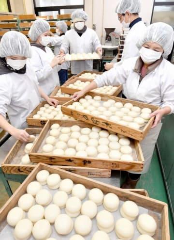 雑煮用などの餅作りに追われる従業員ら=12月28日、福井県福井市西開発1丁目の越前笹木餅
