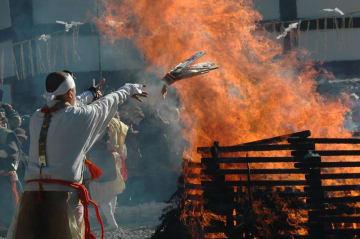 高々と上がる炎の中にお札を投げ入れる僧侶=28日、成田山新勝寺