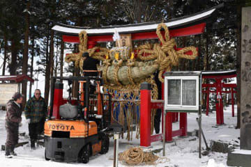 重さ約300キロの大年縄を鳥居に飾り付ける地域住民ら=28日午前11時半ごろ、藤崎町の福島地区