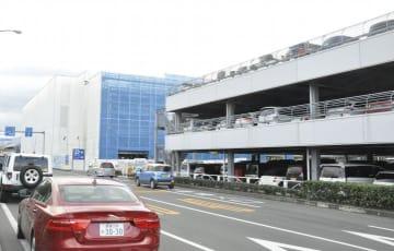 松山空港の既存立体駐車場(手前)と工事中の新立体駐車場(奥)=28日午後、松山市南吉田町