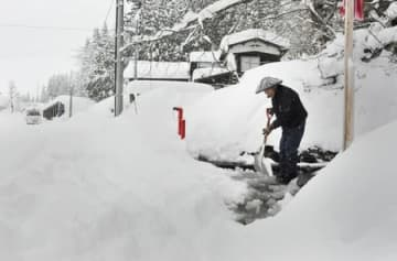 自宅前の道路で除雪作業をする住民=29日午後4時ごろ、津南町秋成