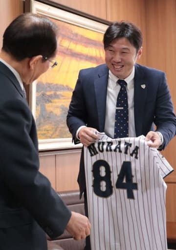 11月の日米野球で着用した侍ジャパンのユニホームを贈る村田さん(右)=佐世保市役所