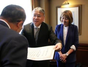 授与式で証書を受け取るイシグロさん(中央)。右は妻ローナさん=7月3日、ロンドン