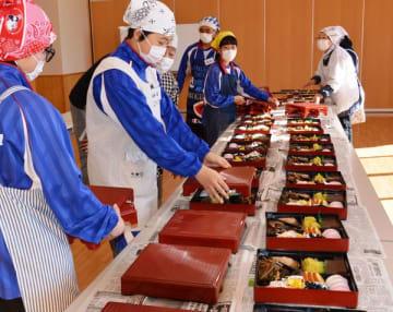 中学生も参加して行われたお節料理の重箱詰め=29日午前、鹿沼市楡木町