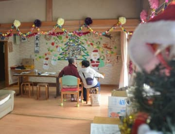 職員手作りのクリスマス飾りに彩られたリビングで別れの時を待つ入所者(左)と職員=二宮町川匂のグループホーム「かわわの家」