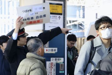 東北・山形新幹線などのホームで、利用者の対応に追われる駅員(左端)=30日午後、JR東京駅