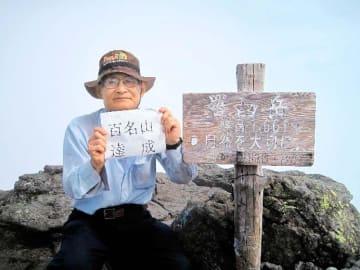 北海道の羅臼岳山頂で、日本百名山踏破の記念写真を撮る真木太一さん=2016年9月(真木さん提供)