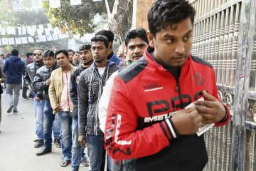 30日、バングラデシュの首都ダッカで議会選の投票所への入場を待つ人々(共同)