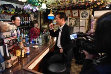洋酒喫茶プリンスで行われた「はちのへ酒場100選」の収録。カクテル「かぶしま」を味わうノブさんと撮影する出町代表(右手前)