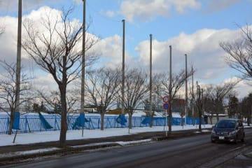 五所川原市営球場の三塁側フェンス。ファウルボールが、市道(手前)を走る車を直撃する事故が発生している=五所川原市不魚住