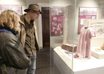 日系人強制収容を伝える特別展を訪れ、展示されたワンピースを見るクリス・チャブさん(奥)と娘のサラさん=2018年12月7日、米ワシントンのスミソニアン米国歴史博物館(共同)