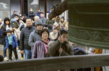 岡山県倉敷市真備町地区の金峯寺で除夜の鐘突きをする人たち。例年深夜に実施していたが、豪雨の影響で地区外で生活する住民も多く昼間に開催された=31日