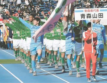 開会式で青森県名産のリンゴを手に入場行進する青森山田の選手
