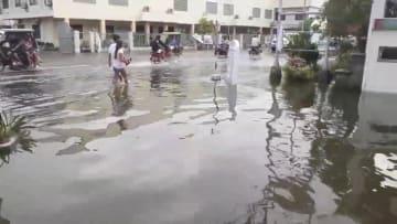 30日、フィリピン北部ルソン島の北カマリネス州で、冠水した道路を歩く人々(Robert Balidoy氏提供・ロイター=共同)