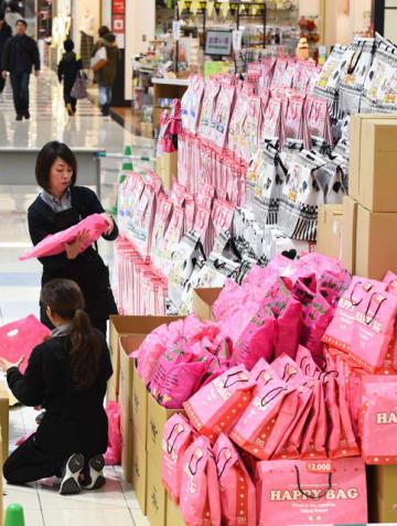 元日の初売りに向け特設コーナーに福袋を並べる店員たち=31日午後、宮崎市・イオンモール宮崎