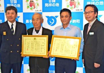副管理者の當山宏町長(右)から感謝状を贈られた謝花良輝さん(右から2人目)、山城甚助さん(同3人目)=嘉手納町役場