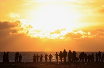 宮城県名取市閖上地区の海岸で初日の出を見る人たち=1日午前7時7分