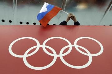 2014年ソチ五輪の会場で、五輪のロゴの上で振られるロシア国旗=ソチ(AP=共同)