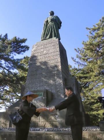 坂本龍馬宛ての年賀はがきを受け取る、高知県立坂本龍馬記念館の高松清之館長(右)=1日、高知市