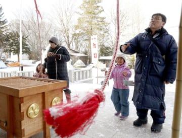 昨年9月の地震で大きな被害を受けた厚真神社で、初詣する家族連れ=1日、北海道厚真町
