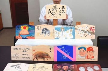 縁起物や話題物、イノシシなどが描かれた著名人の絵馬=川崎市川崎区の稲毛神社