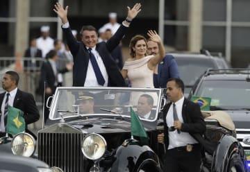 ブラジル大統領就任式の後、オープンカーに乗って手を振るボルソナロ氏(中央左)と妻ミシェリさん=1日、ブラジリア(AP=共同)