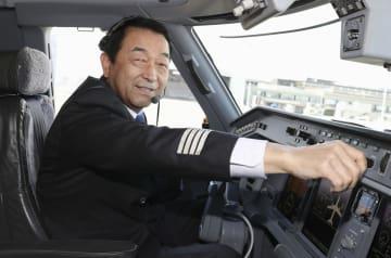 引退の日を迎え、駐機中の機内で撮影に応じるフジドリームエアラインズの機長秋田芳男さん=2日、愛知県営名古屋空港