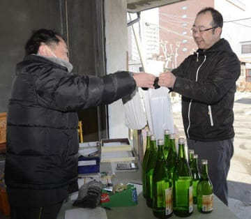 純米新酒「新春しぼりたて生」を受け取る購入者(右)=1日、八戸市
